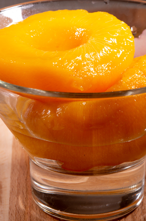 Glass with sweet canned peaches closeup with blur Stock Photo