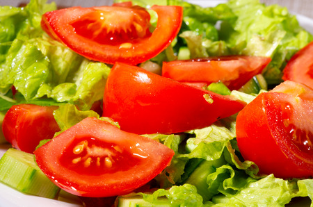 Fragment of dish made from pieces of fresh cucumbers, tomatoes, spinach and lettuce close-up with blur. Stock Photo
