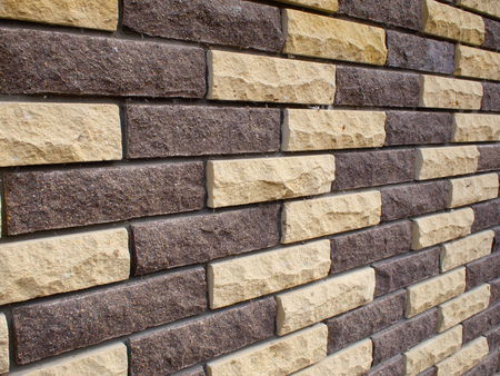 Diagonal view of a wall of yellow and brown bricks close-up as background