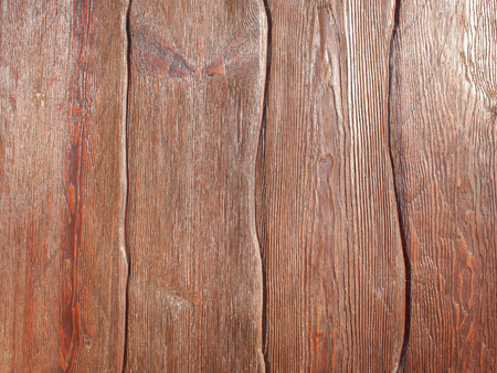 Wooden background of brown vertical boards with uneven shapes