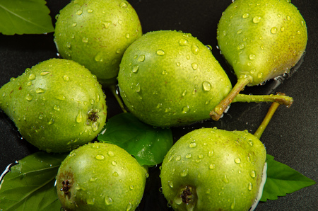 Green pears on a dark background sprinkled with water close-up