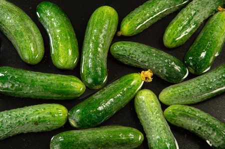 Top view of green cucumbers in water for washing as food background