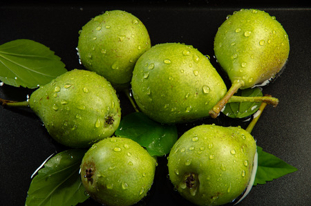 Green pears with leaves are in the water on a dark background