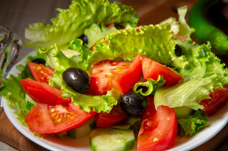 Dish with fresh salad of tomatoes, olives and cucumbers with olive oil