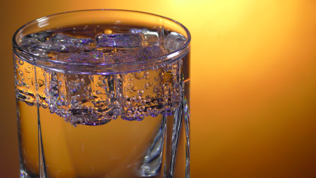 Glass with soda water and ice cubes with bubbles on a bright background. Close up view Stock Photo