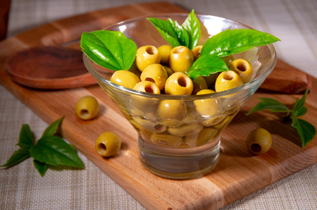Pitted olives in a glass cup are poured with olive oil