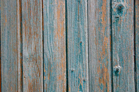 Background of wooden boards with old paint and vertical slats. Close-up view with bright lighting.