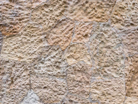 Brown wall of stone blocks of irregular shape and uneven surface for use as a background close up.