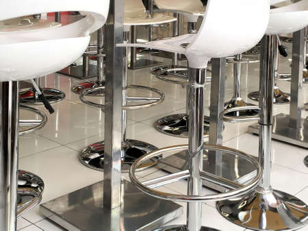 Fragments of bar stools and metal racks on ceramic tiles close-up for use as background.