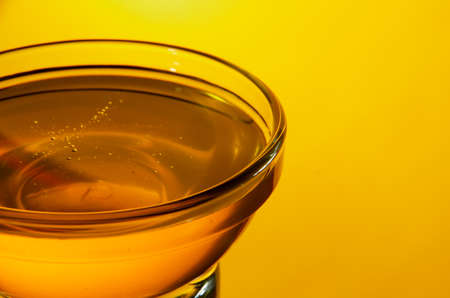 Close-up side view of a small glass bowl of honey on a yellow background with backlight. Shallow focus. Stock Photo