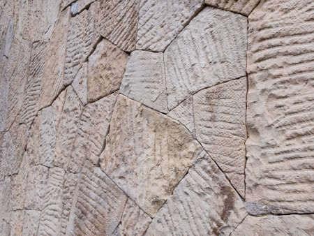 Angle view on brown wall of stone blocks of irregular shape and uneven surface for use as a background close up.