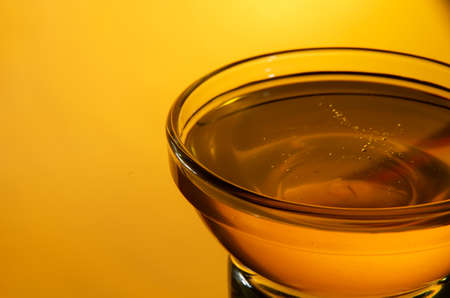 Glass bowl with honey on a bright yellow background close-up with copy space. Stock Photo