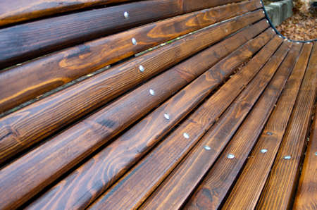 Angled view of a park bench with natural wood texture close up, shallow focus for use as autumn background.
