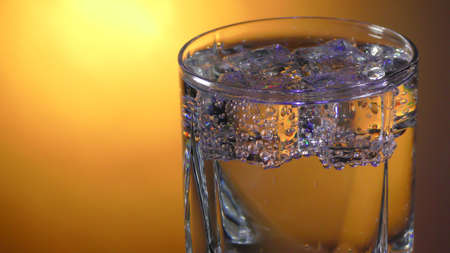 Transparent glass with soda water and ice on a bright background with a gradient close-up. Stock Photo