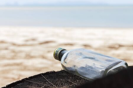 Empty used dirty glass bottles on the seaside. Ecological problem and environmental pollution. Glass bottles are non-degradable and abandoned on the coast.
