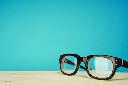 Black glasses on a blue background