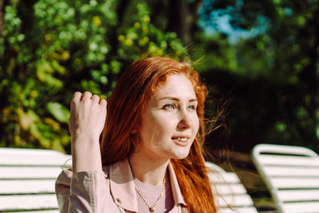 Red-haired girl in the park on the bench