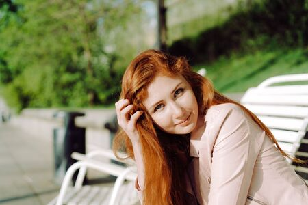 slow motion: Portrait of a pretty red-haired teenage girl. She smiles and dreams. The sun beautifully illuminates his hair. 4K slow motion video Stock Photo