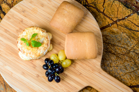 warm cheese with grapes and buns Stock Photo