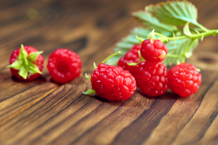 Redcurrant, raspberry and red berries on old wooden table, mix of red color vitamins concept
