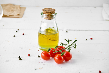 tomatoes with oil bottle on white wooden background