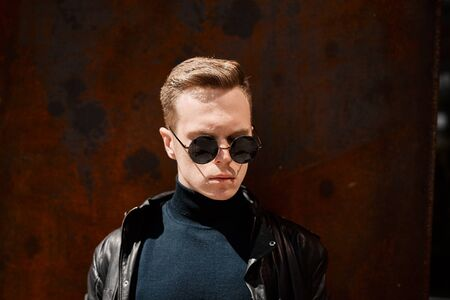 portrait of a handsome young man in sunglasses on a rusty iron background Stock Photo