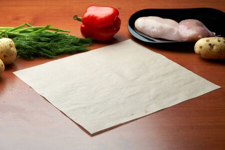 Natural vegetables, potatoes, green onions, dill, paper, chicken breast on a wooden background, top view