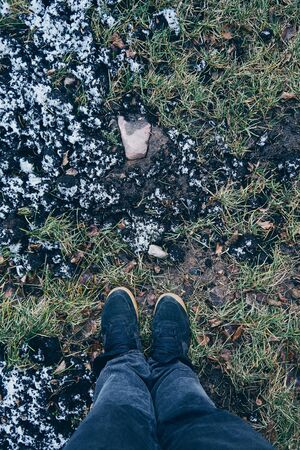 feet sneakers grass first snow blue boots of the snow on the grass Reklamní fotografie