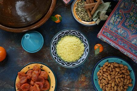 Bulgar porridge in a ceramic painted Eastern plate in the center of the table Mandarin dried apricots nuts almonds Eastern cuisine