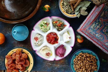 Sauces and salads mix in a ceramic painted Oriental plate in the center of the table Mandarin dried apricots nuts almonds Eastern cuisine