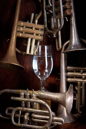 pipes of wind instruments on a wooden background in the center of a gloved hand with a ring holding a glass with a drink.