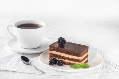 Delicious chocolate cake in white plate on white wooden table background, closeup Reklamní fotografie