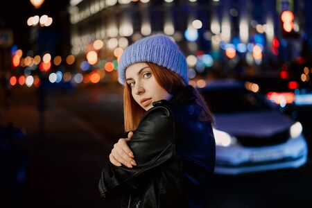 beautiful red-haired girl in blue hat at night