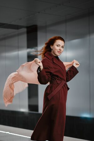 Red-haired girl in the subway, red coat