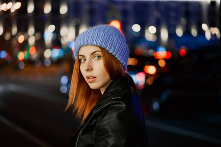 beautiful red-haired girl in blue hat at night Reklamní fotografie