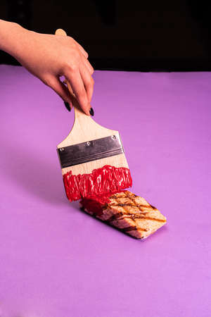 Paint fried meat with red paint with a brush on a lilac background Reklamní fotografie