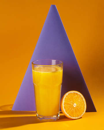 freshly squeezed orange juice half an orange on the background of a lilac pyramid on an orange background