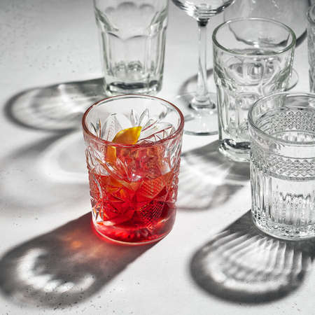 Cocktail with lemon in a glass against the background of many crystal and glass glasses Reklamní fotografie