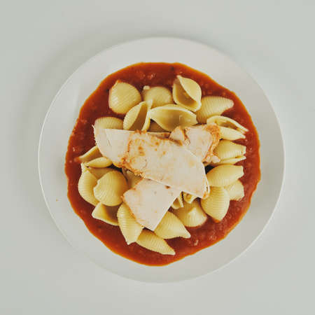 Pasta with tomato sauce and chicken breast pieces on a plate