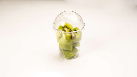slices of green kiwi in a plastic cup with a lid