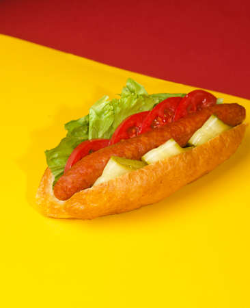 hot dog on yellow red background bun with sausage salad and cucumber