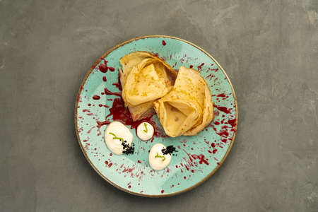 pancakes with sour cream jam on a blue plate on a gray background