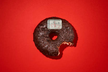 Diet slimness weight loss scale scales chocolate coated doughnut bitten on a red background