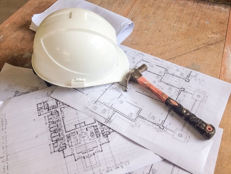 construction: Shop drawing and safety helmet with hammer on table