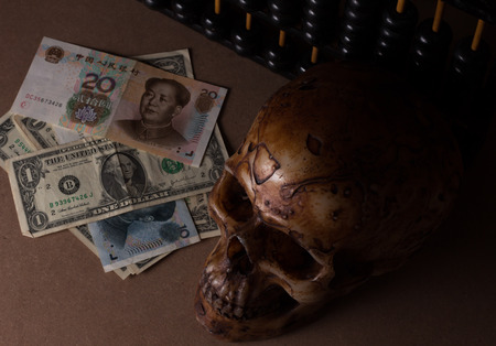 stilllife: skull on old wood with banknote yuan and dollar in still-life