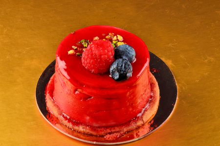 Beautiful cake with red glossy glaze in a restaurant.