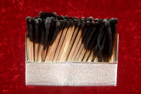Burnout at work and over exhausted concept. Line of matches and all burnt. With red background. Zdjęcie Seryjne