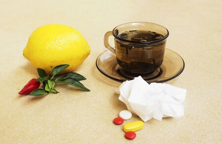 handkerchiefs: Hot tea for colds, pills and handkerchiefs on table,lemon and peppers, natural remedy