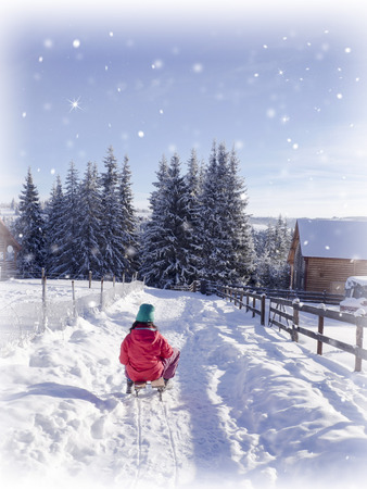 frostbitten: Girl on sledge in winter snow. Winter sport holiday Stock Photo