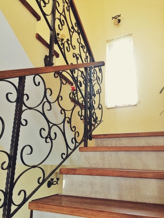 remodeled: house interior with shiny tile floor. Marble staircase with black wrought iron railing